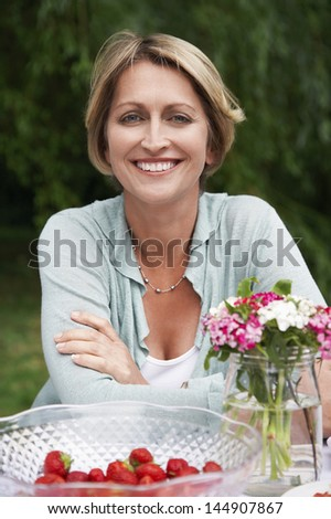 Portrait of smiling middle aged woman sitting at table in garden - stock photo