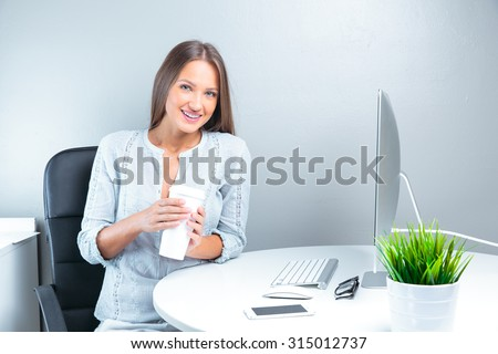 Portrait of smiling modern business woman in office working and drinking coffee - stock photo