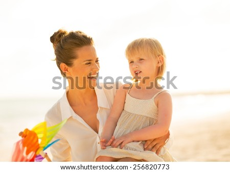 Portrait of smiling mother and baby girl with colorful windmill toy on beach at the evening - stock photo