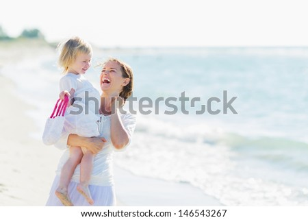 Portrait of smiling mother and baby on beach - stock photo