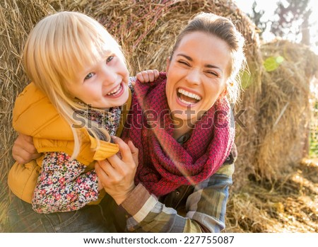 Portrait of smiling mother and child near haystack - stock photo