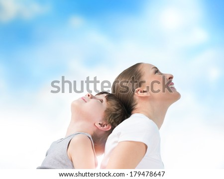 Portrait of smiling mother and her son standing back to back outdoors against sky - stock photo