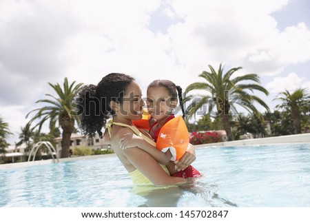 Portrait of smiling mother holding daughter in swimming pool - stock photo