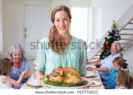 Portrait of smiling mother with Christmas meal at dining table - stock photo