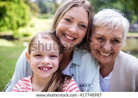 Portrait of smiling multi-generation family in the park - stock photo