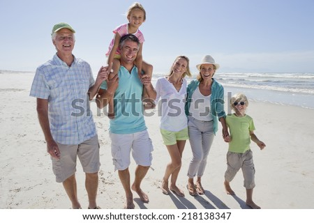 Portrait of smiling multi-generation family walking on sunny beach - stock photo