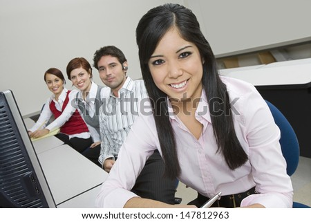 Portrait of smiling multiethnic businesspeople sitting at office desk - stock photo