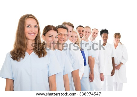 Portrait of smiling multiethnic medical team standing in line against white background - stock photo