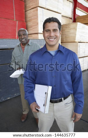 Portrait of smiling multiethnic men with clipboards in front of stacks of wood in warehouse - stock photo