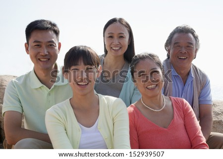Portrait of smiling multigenerational family sitting on the rocks outdoors, China - stock photo