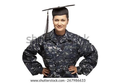 Portrait of smiling navy female sailor wearing graduation cap against white background - stock photo