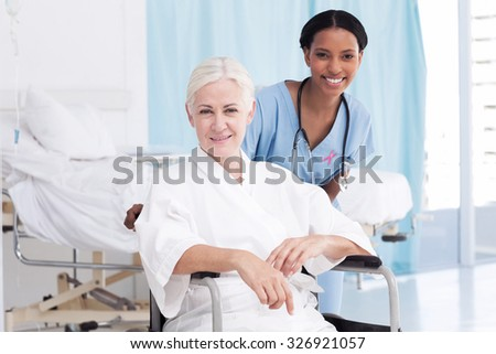 Portrait of smiling nurse with female patient in wheelchair against pink awareness ribbon - stock photo