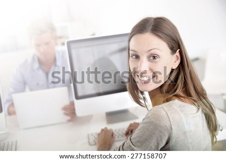 Portrait of smiling office worker in front of desktop - stock photo