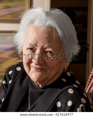 Portrait of smiling old woman at home - stock photo