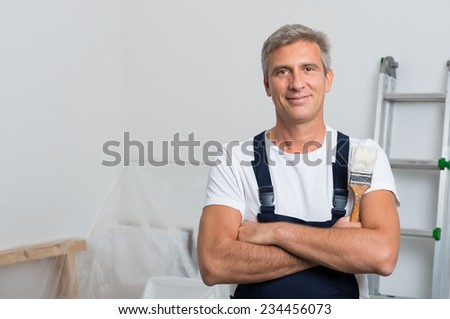 Portrait Of Smiling Painter With Arm Crossed Holding Paintbrush At Home - stock photo