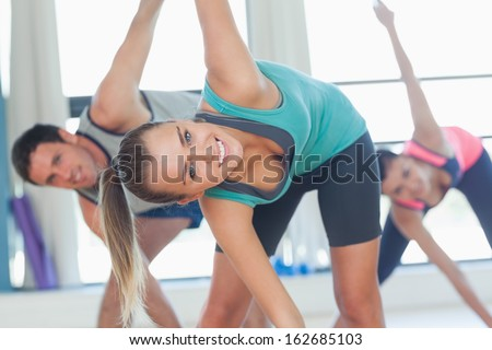 Portrait of smiling people doing power fitness exercise at yoga class in fitness studio - stock photo