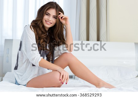 Portrait of smiling positive carefree young woman sitting on white bed at home - stock photo