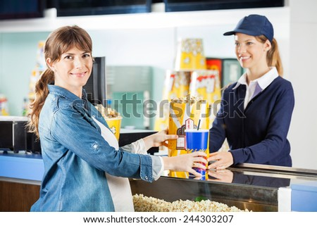 Portrait of smiling pregnant woman buying popcorn and drink from seller at cinema concession counter - stock photo