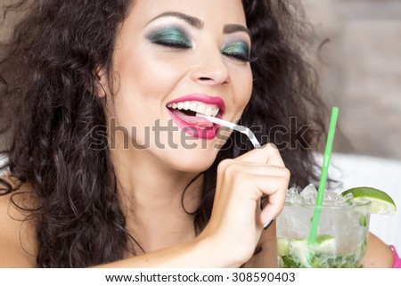 Portrait of smiling pretty brunette woman with curly hair and bright makeup with alcoholic mojito cocktail from mint soda light rum ice cubes and lime with straw, horizontal picture - stock photo