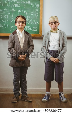 Portrait of smiling pupils dressed up as teachers in a classroom in school - stock photo