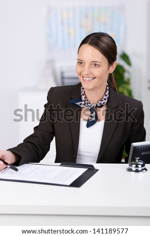 Portrait of smiling receptionist at counter in office - stock photo