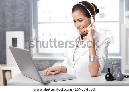 Portrait of smiling receptionist using laptop computer and headset at office desk. - stock photo