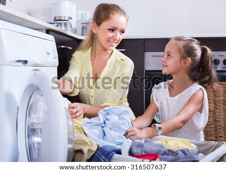 Portrait of smiling russian mom and daughter with bin near washing machine  - stock photo