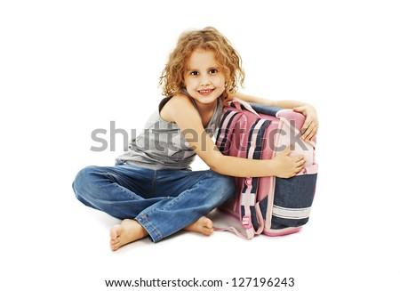 Portrait of smiling school girl hugging rucksack. Isolated on white background - stock photo