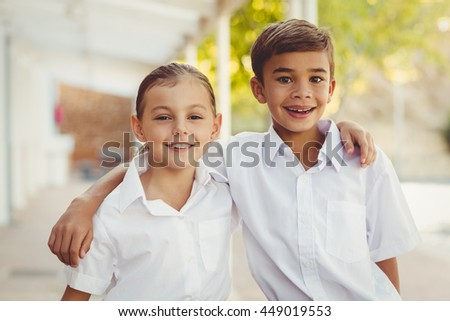 Portrait of smiling school kids standing with arm around in corridor at school - stock photo