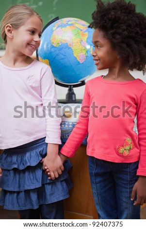 Portrait of smiling schoolgirls holding hands in a classroom - stock photo