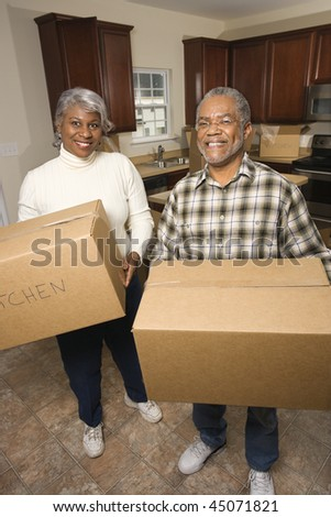 Portrait of smiling senior african american man and woman with moving boxes in a new home.   Vertical shot. - stock photo