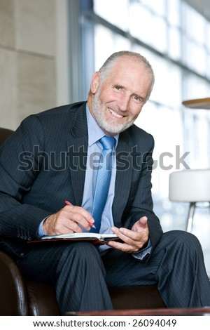 Portrait of smiling Senior business man writing on notepad - stock photo