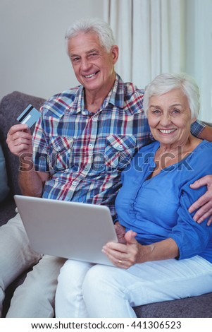 Portrait of smiling senior couple with credit card and laptop at home - stock photo