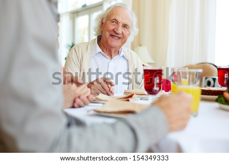 Portrait of smiling senior man at festive table looking at young man before prayer - stock photo
