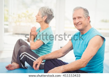 Portrait of smiling senior man sitting beside wife performing yoga at home - stock photo