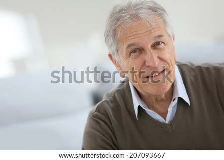 Portrait of smiling senior man sitting on sofa at home - stock photo