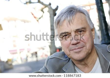 Portrait of smiling senior man standing outside - stock photo