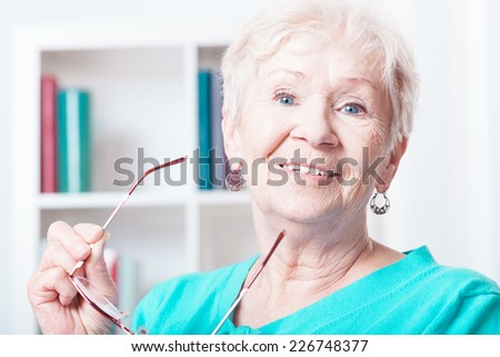 Portrait of smiling senior woman at her house - stock photo