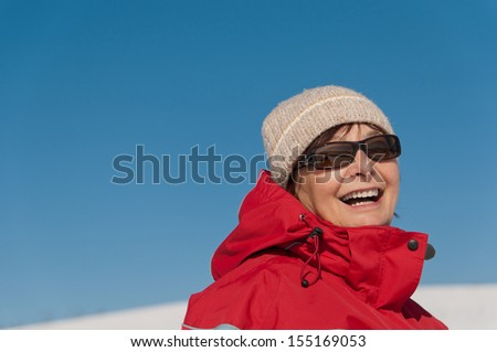 Portrait of  smiling senior woman in winter - blue sky in background - stock photo