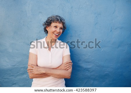 Portrait of smiling senior woman standing with her arms crossed and looking away at copy space against blue background. Caucasian middle aged female looking happily at copy space. - stock photo