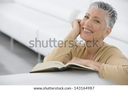 Portrait of smiling senior woman with book on sofa at home - stock photo