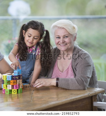 Portrait of smiling senior woman with granddaughter playing with alphabet blocks at home - stock photo