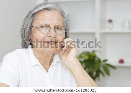 Portrait of smiling senior woman with hand on chin looking at camera. - stock photo