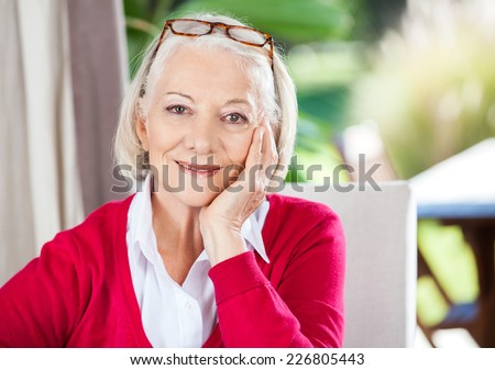 Portrait of smiling senior woman with hand on chin sitting at nursing home - stock photo