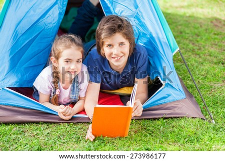 Portrait of smiling siblings reading book in tent at park - stock photo