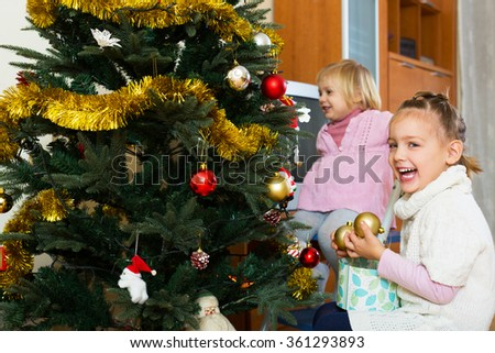 Portrait of smiling sisters decorate Christmas tree indoor - stock photo