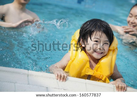 Portrait of smiling son in water and holding pools edge with family in background - stock photo