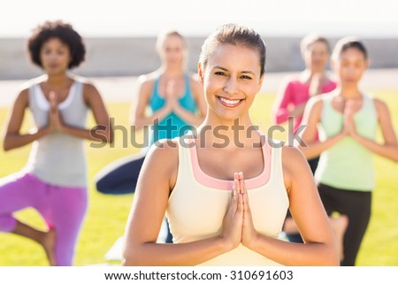 Portrait of smiling sporty brunette doing yoga in yoga class in parkland - stock photo