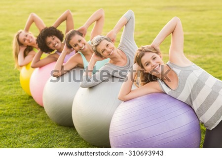 Portrait of smiling sporty women working out with exercise balls in parkland - stock photo