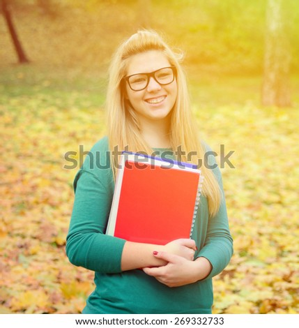 Portrait of smiling student girl holding books - stock photo